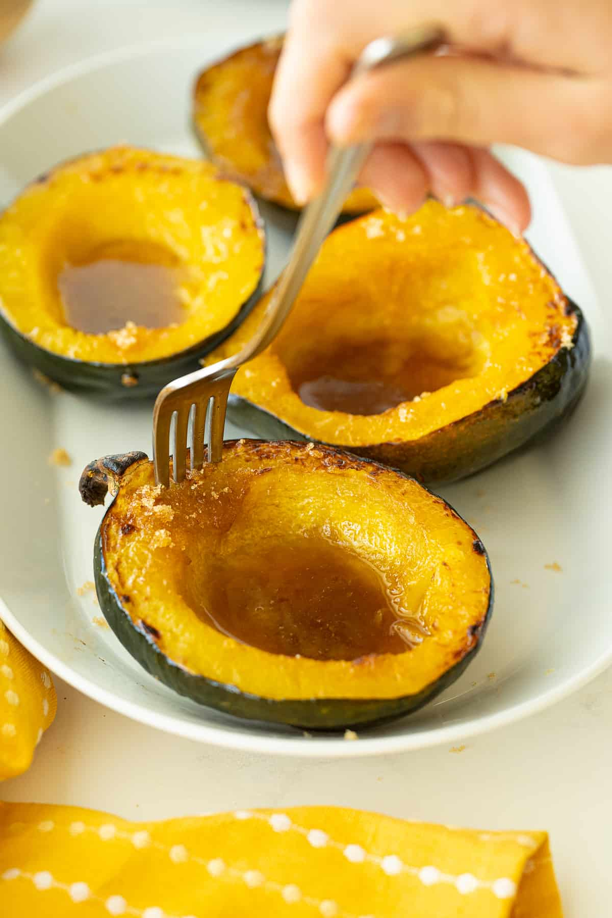 using a fork to have a part of baked cuts of Acorn Squash