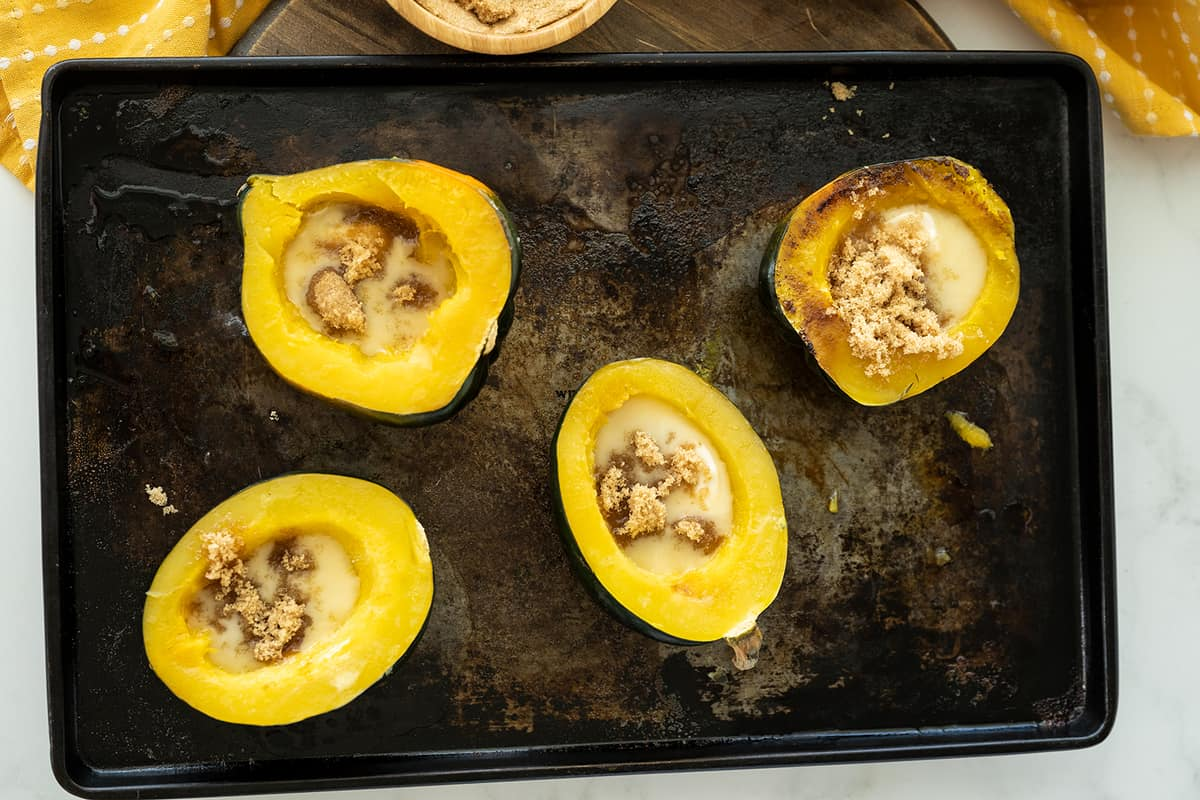 Acorn Squash with butter and brown sugar on center placed in a baking sheet
