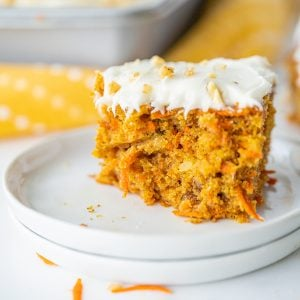 A slice of carrot cake on a plate with cream cheese icing