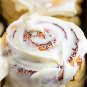 close up of a cinnamon bun with cream cheese icing slathered on top