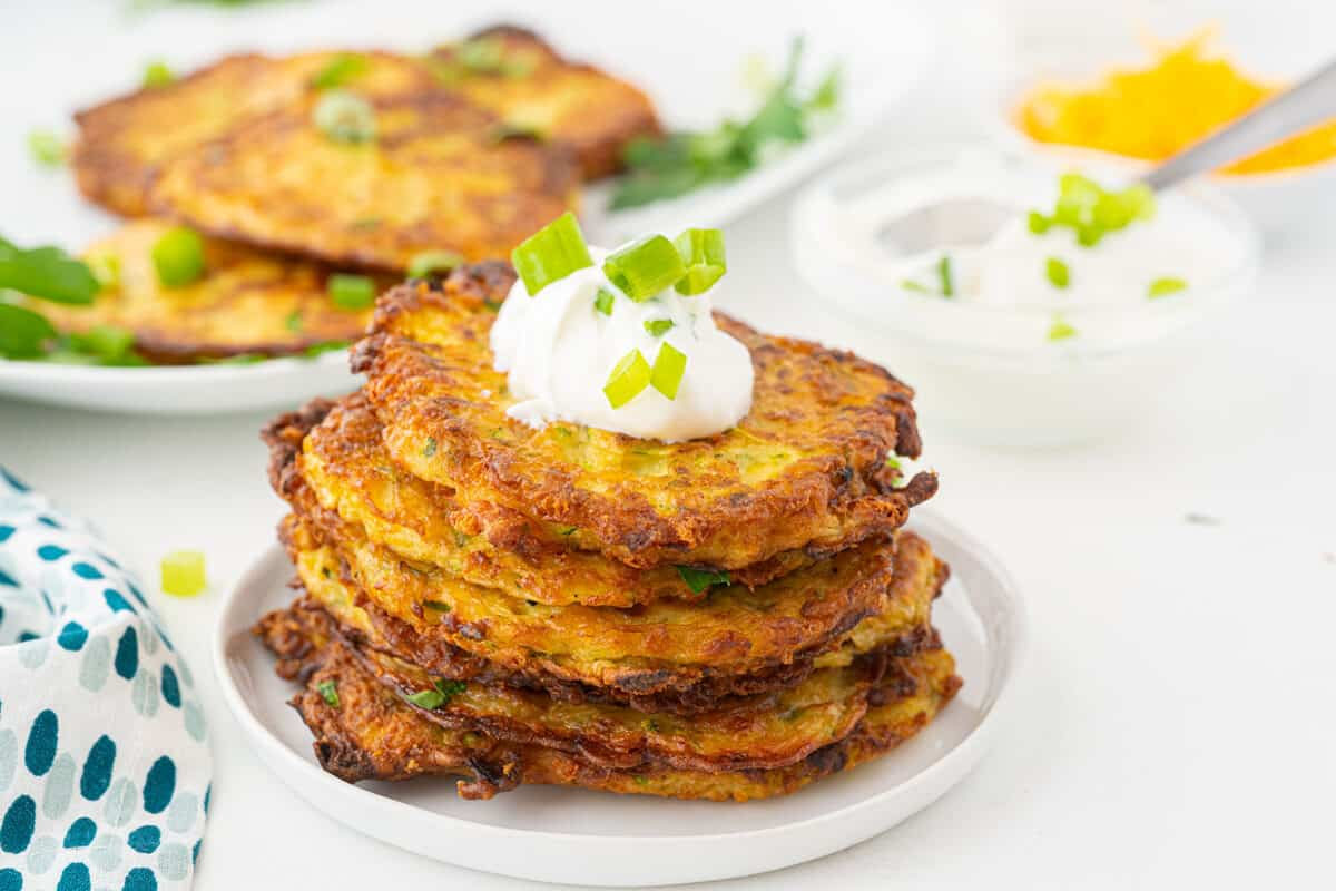 zucchini fritters on a white plate with sour cream on top of them