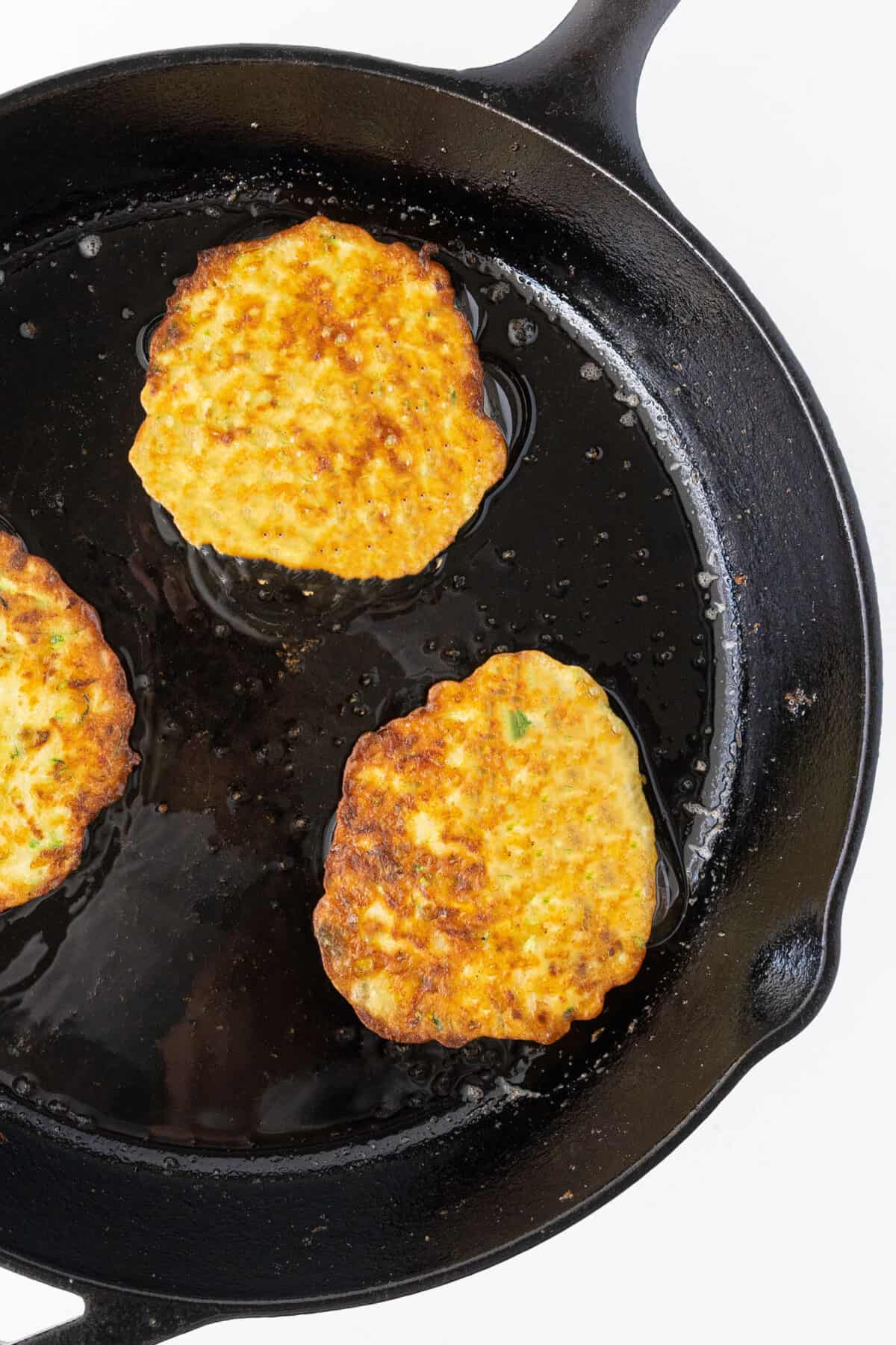 cooking three zucchini fritters in a cast iron pan