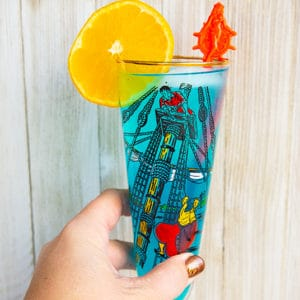 woman's hand holding a blue AMF cocktail drink garnished with an orange slice that's in a vintage pirates motif glass