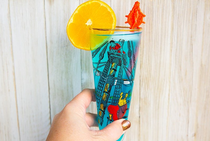 A blue AMF cocktail drink garnished with an orange slice that's in a vintage pirates motif glass