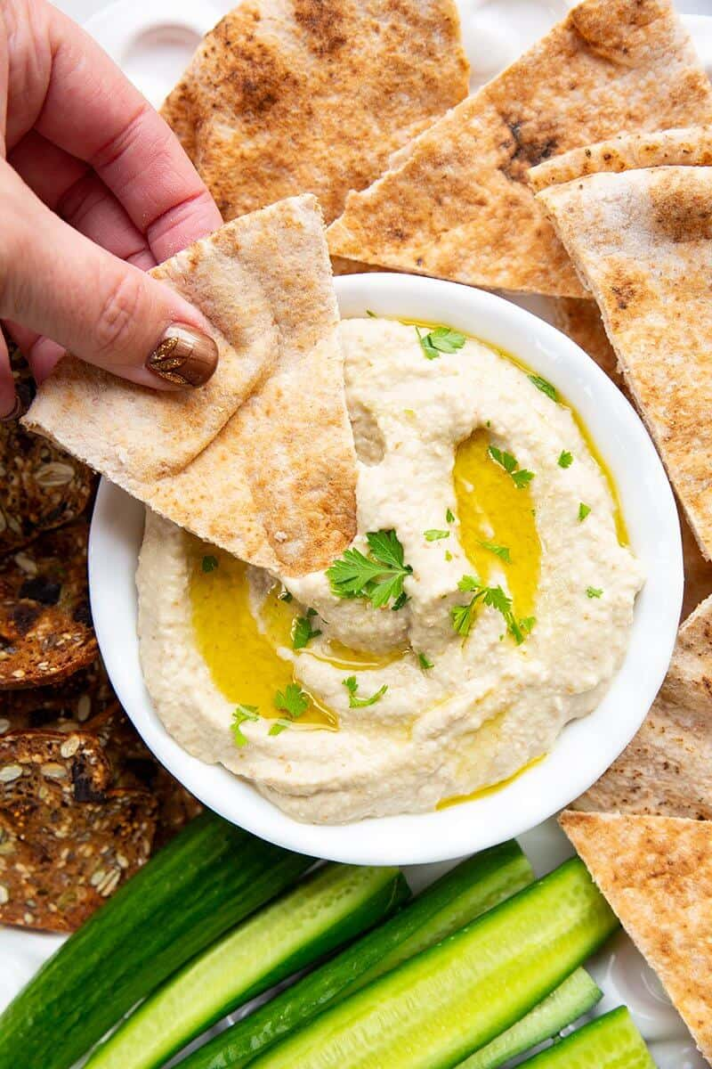 dipping an oven baked pita chip into Baba Ganoush