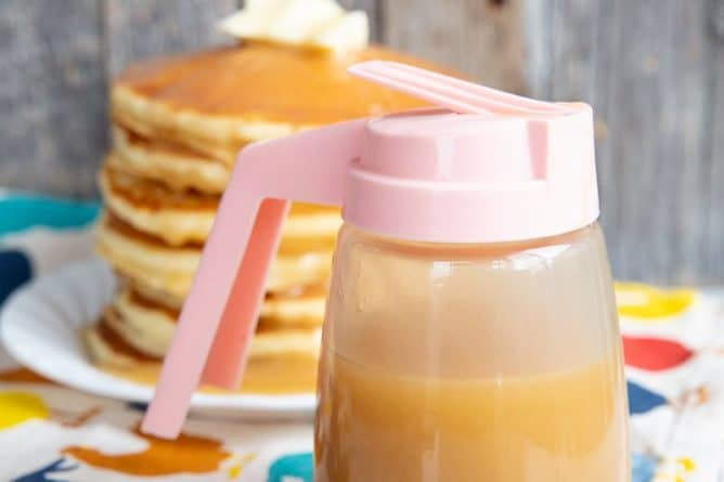 close up of Brown Sugar Sauce in a small pitcher like container, stack of pancakes in white plate on the background