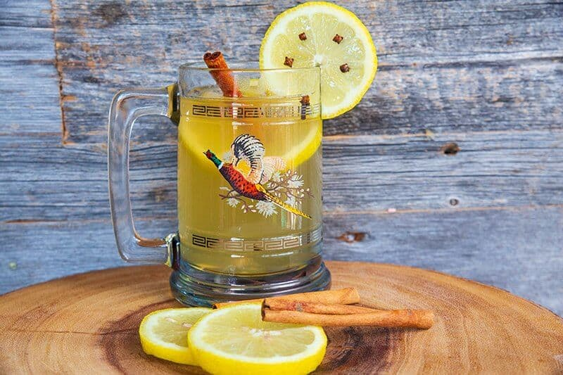 A classic hot toddy made with Scottish whisky in a vintage pheasant glass mug garnish with cinnamon sticks and slices of lemon