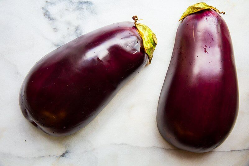 2 pieces of round and fat whole globe eggplant on marble background