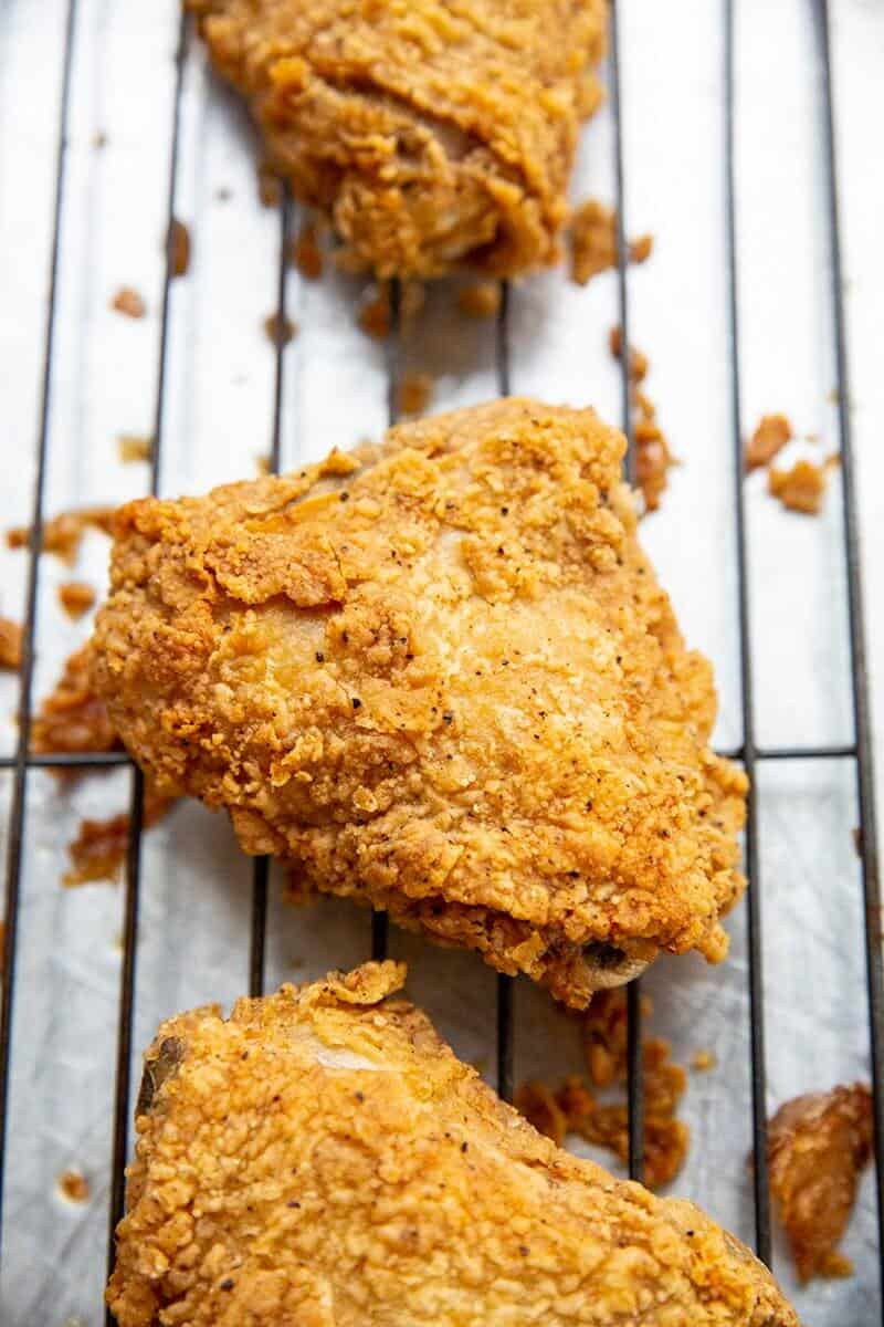 Crispy Fried Chicken in black wire baking rack with spaces in between them
