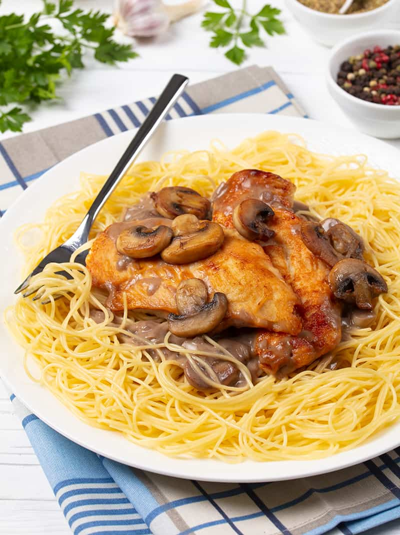 checkered blue kitchen towel underneath white plate with Chicken Marsala on angel hair pasta and a fork on it, parsley leaves and some ingredients on its background