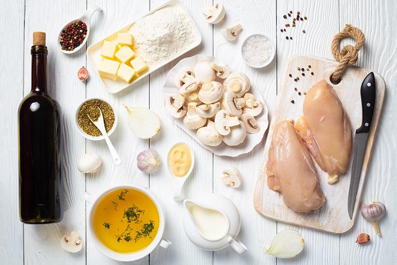 Chicken Marsala ingredients on a white wood background
