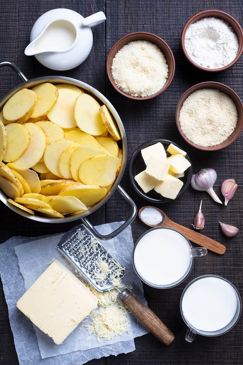 Potatoes Au Gratin ingredients on dark wood background