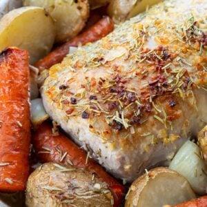 close up seasoned boneless Pork Loin Roast in a pan with potatoes and carrots