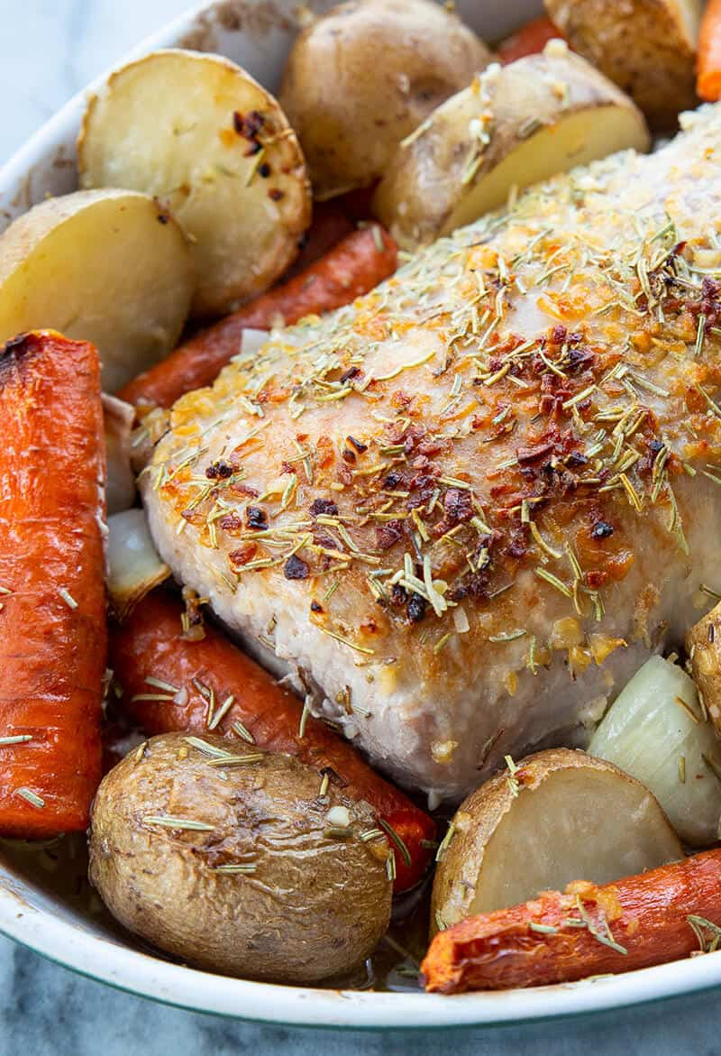 close up seasoned boneless Pork Loin Roast in a pan with potatoes and carrots