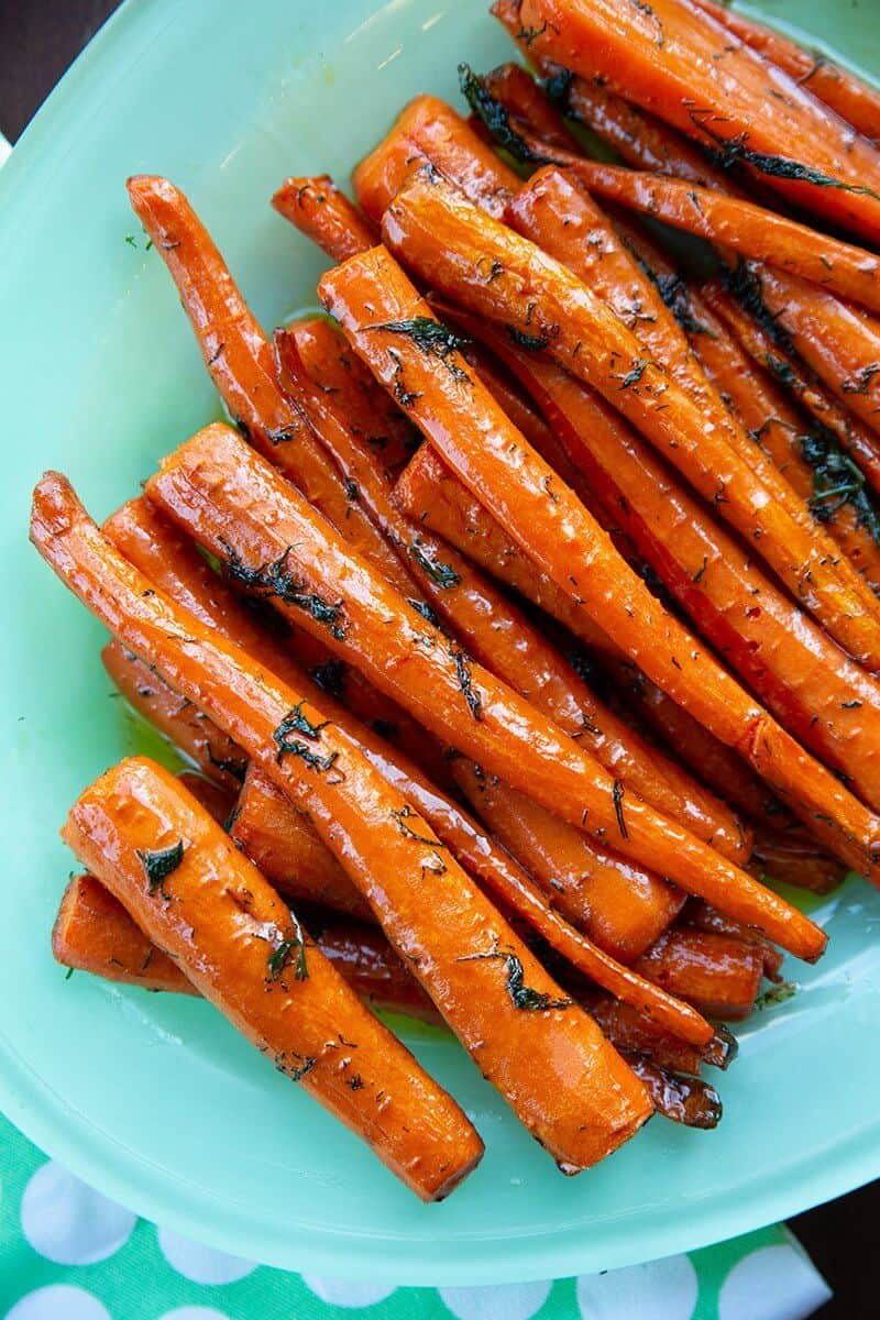 close up roast sliced carrots with dill in a baking pan