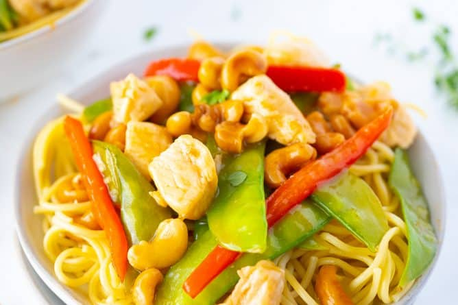 Cashew Chicken Stir Fry in a White Plate with Noodles