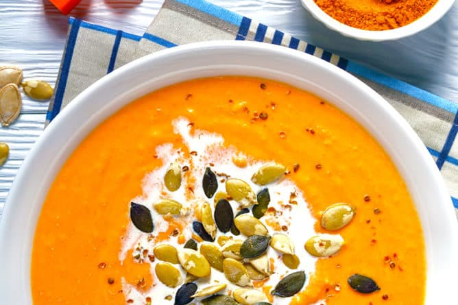 close up folded kitchen cloth underneath a white large bowl with Curried Pumpkin Soup topped with extra cream and pepitas, a cup of curry powder and slice of pumpkin on its side