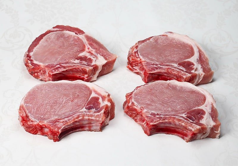 Four raw, thick bone in pork chops on white background