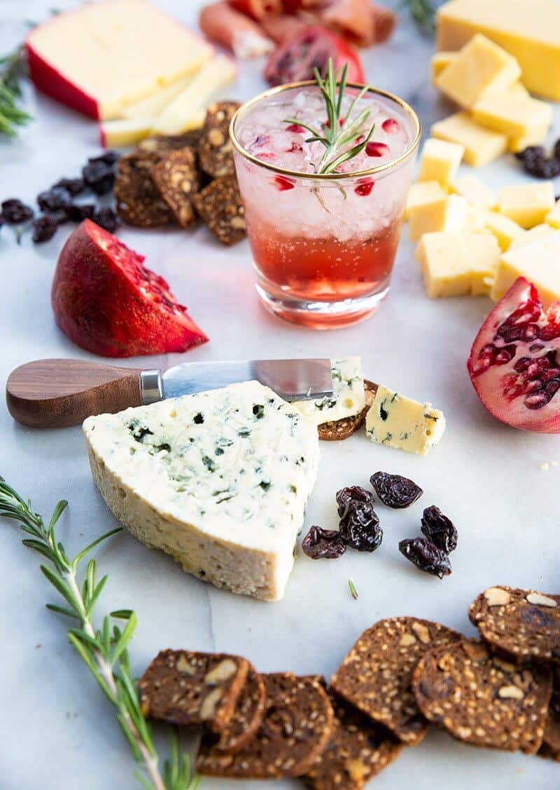 Perfect Cheeseboard with the other food items and a glass of Pomegranate Gin Fizz