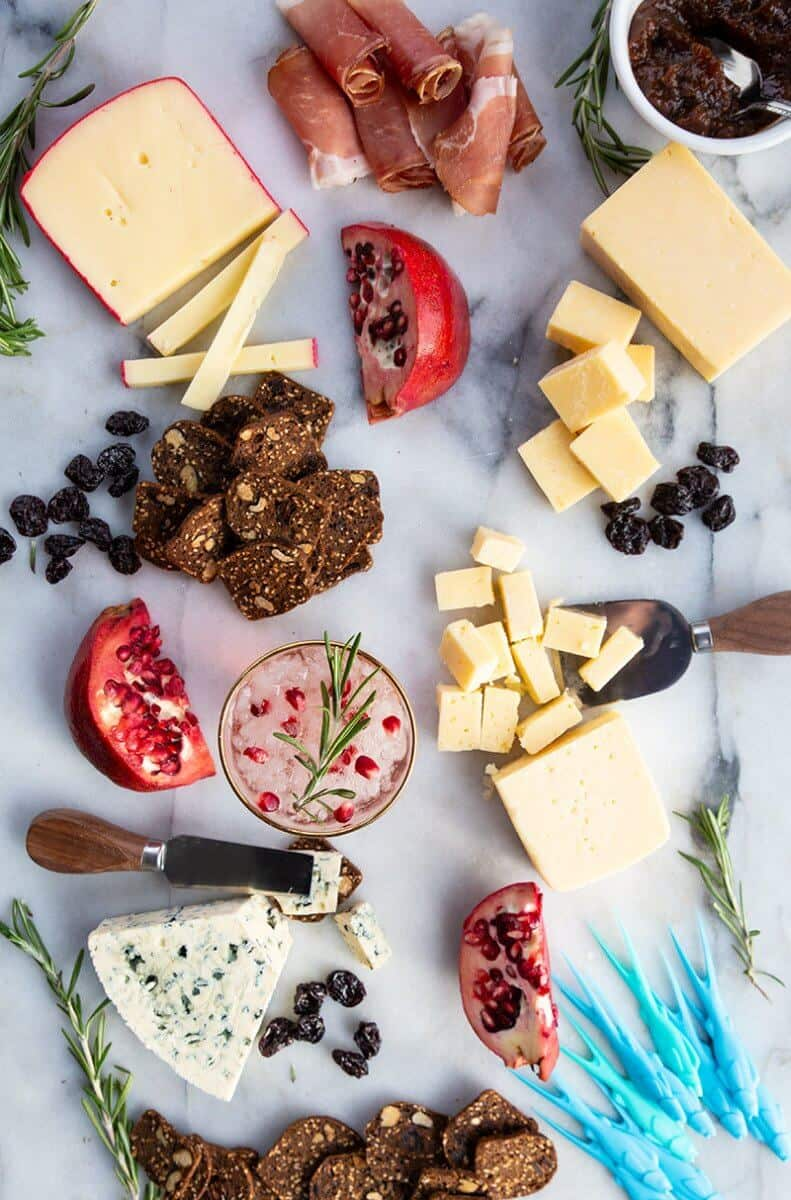 Perfect Cheeseboard with the other food items like Dried cherries, Rosemary Sprigs and Sliced Pomegranates