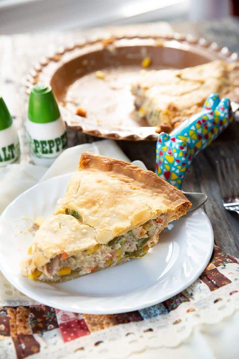 creamy slice of Turkey Pot Pie with poultry seasoning, a pie pan in the background