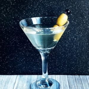 Dirty Martini served in a martini glass with olives as a garnish