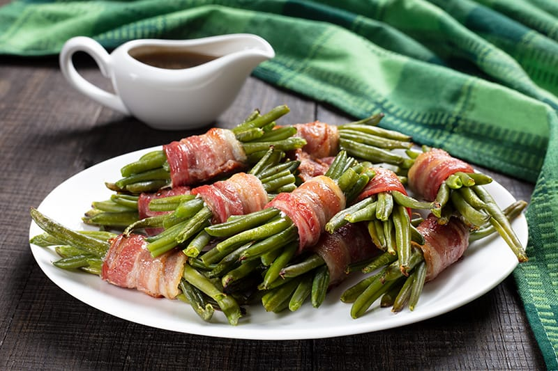 Bacon Wrapped Green Bean Bundles in a white large plate and sauce in white ceramic cup