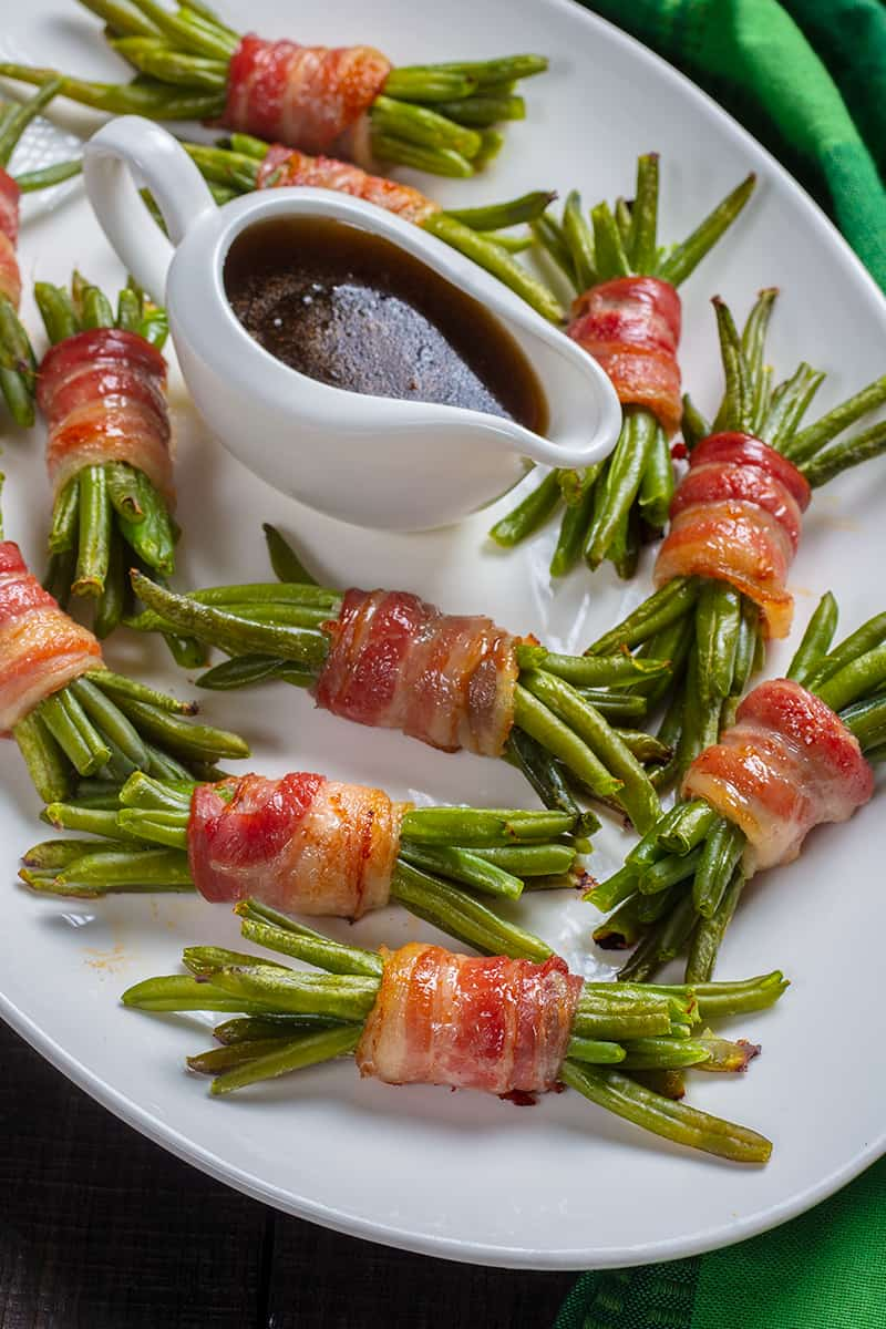 bacon wrapped green bean bundles with a cup of sauce at the middle of the large white plate