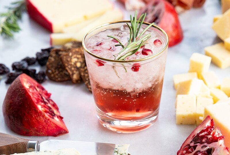 a glass of Pomegranate Gin Fizz in Cheeseboard with a sliced Pomegranate