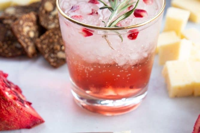 a glass of Pomegranate Gin Fizz garnish with rosemary sprig