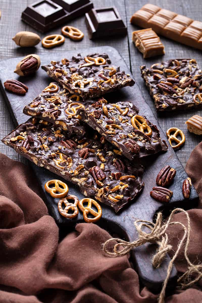 brown tablecloth underneath a wooden chopping board with Turtle Chocolate Bark, crushed pretzels, pecans, bakers chocolate and caramels around it