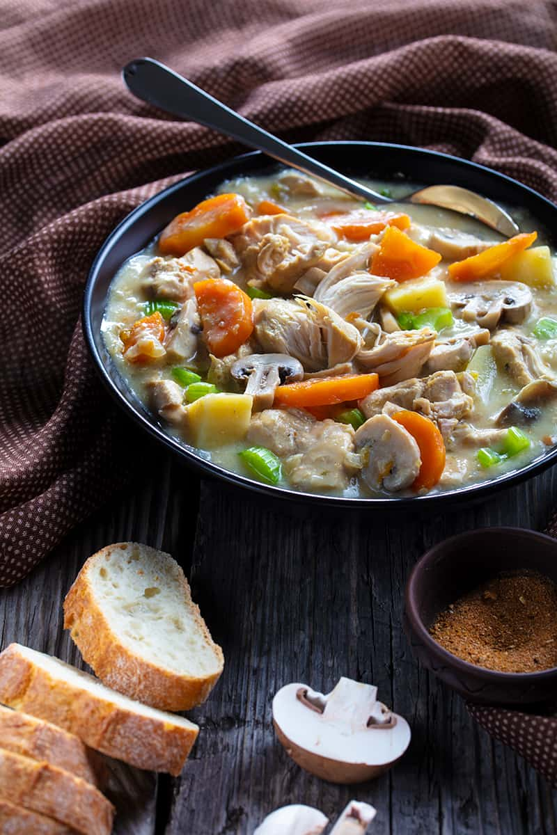 some french bread slices, mushroom slices and a brown table cloth around the large soup bowl of slow cooker chicken stew with spoon