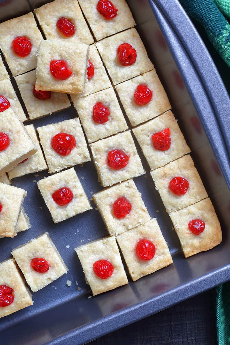 close up Shortbread Bites with candied cherries on top in a large baking sheet