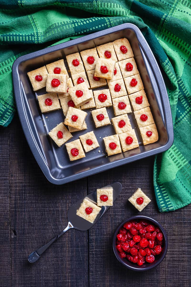 large baking sheet with Shortbread Bites with candied cherries, green tablecloth and some candied cherries at the side
