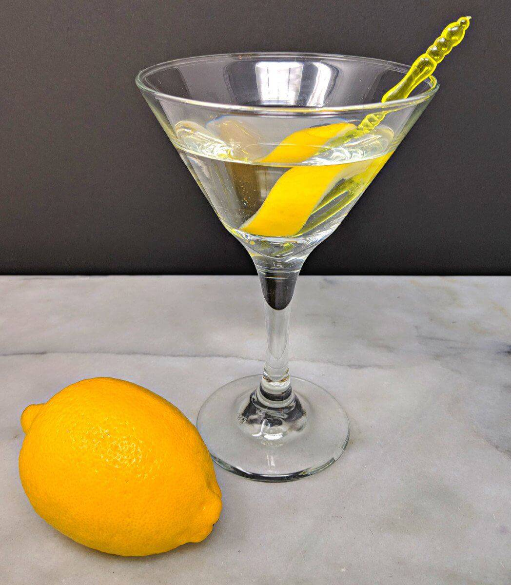 Top down shot of Vesper Martini and a fresh lemon on a marble table