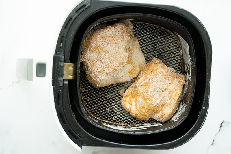 container with chicken inside the air fryer