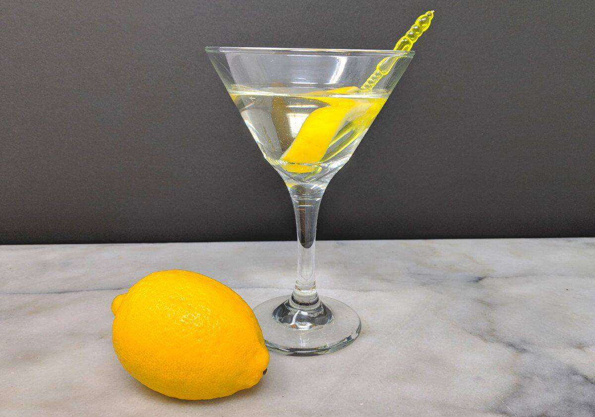 a glass of Vesper Martini garnish with a lemon twist and a fresh lemon on a marble table