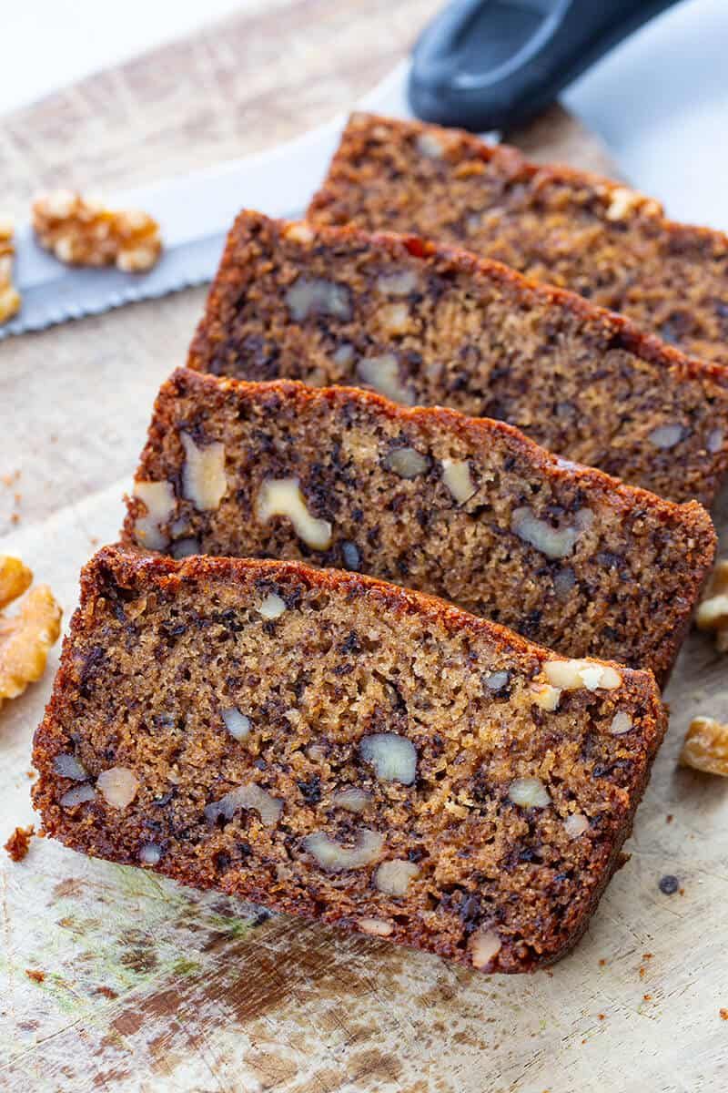 close up slices of Banana Nut Bread in a wood cutting board