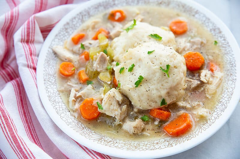 Chicken and Dumplings in a large white bowl with sauce and vegetables