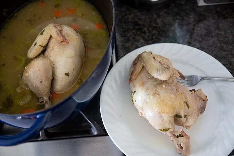 Removing the chicken and vegetables from the Dutch oven and placing it into white plate