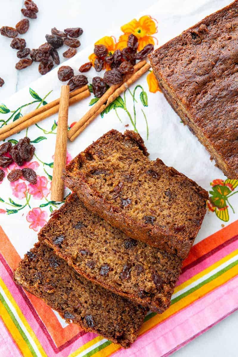 Raisins, cinnamon sticks and a loaf and slices of Cinnamon Raisin Banana Bread