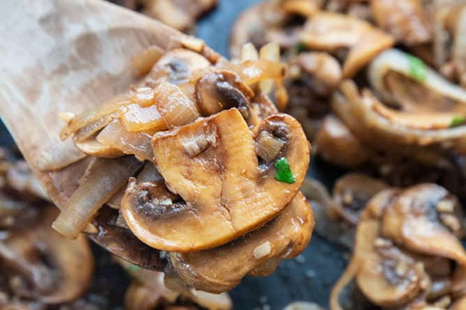 wooden cooking spoon with some Sauteed Mushrooms and Onions