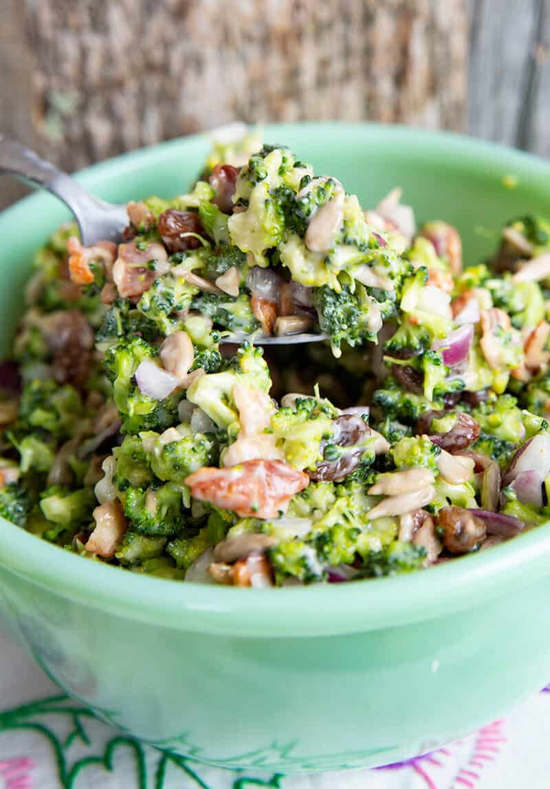 close up Bacon Broccoli Salad Recipe in a green Jadeite bowl with a spoon