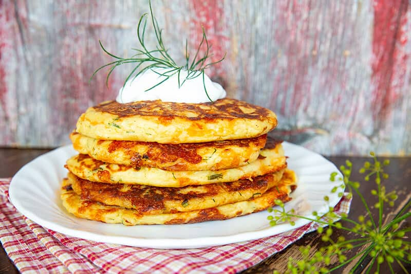 stack of Cheesy Dill & Garlic Mashed Potato Cakes with a dollop of sour cream on top