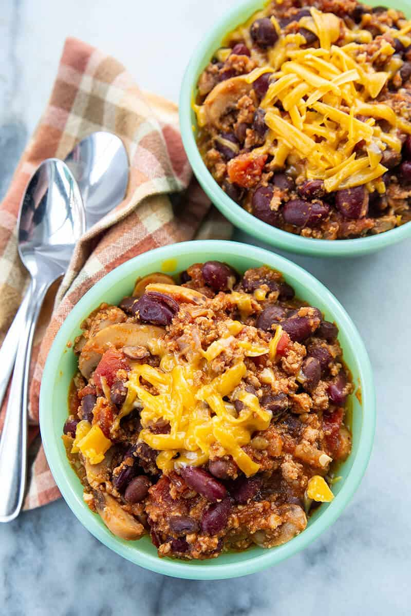 Ground Turkey Chili in small bowls with grated cheese on top, kitchen towel underneath 2 spoons