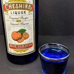 a shot glass with Blue Curaçao and a Bottle of Cheshire Brand Blue Curacao