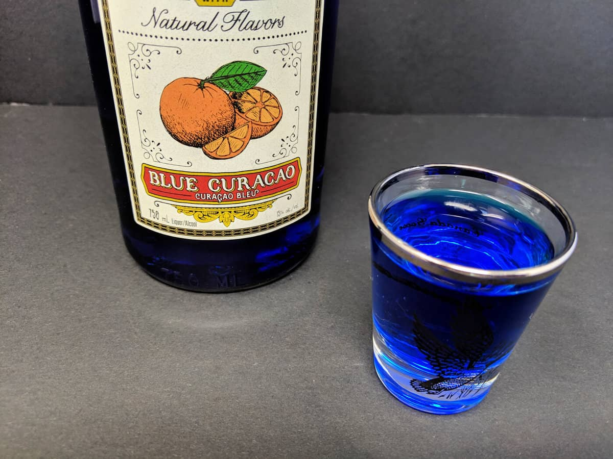 a shot glass with Blue Curaçao and a Bottle of it