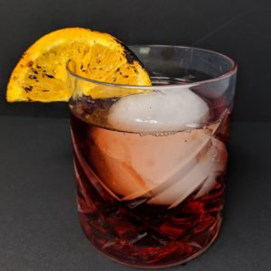 close up Negroni Cocktail in an old fashioned glass with a large ice cube and a slice of burnt orange