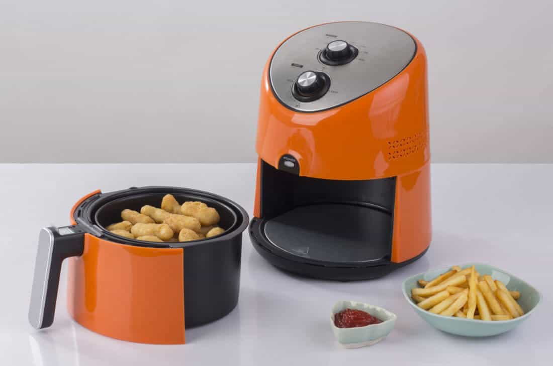 orange color Air fryer machine with chicken and french fries, dipping sauce beside