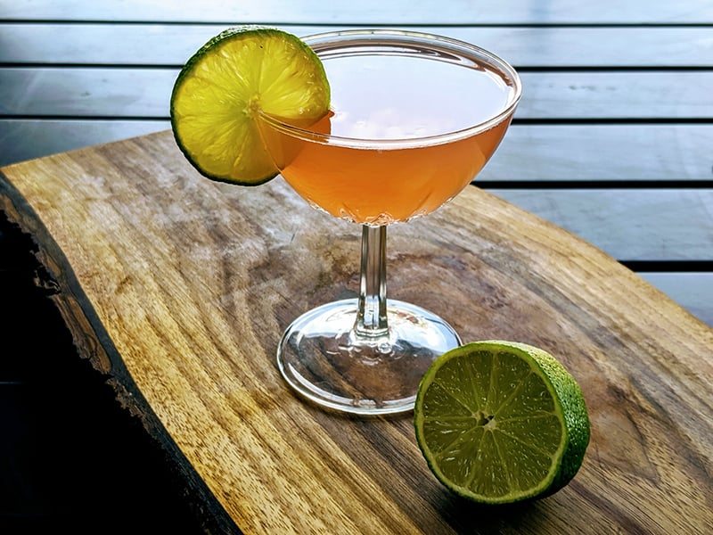 Hemingway Daiquiri in a coupe garnished with lime slice on a wood board with half of a lime.